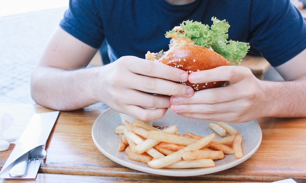 man holding cheeseburger behind plate of fries